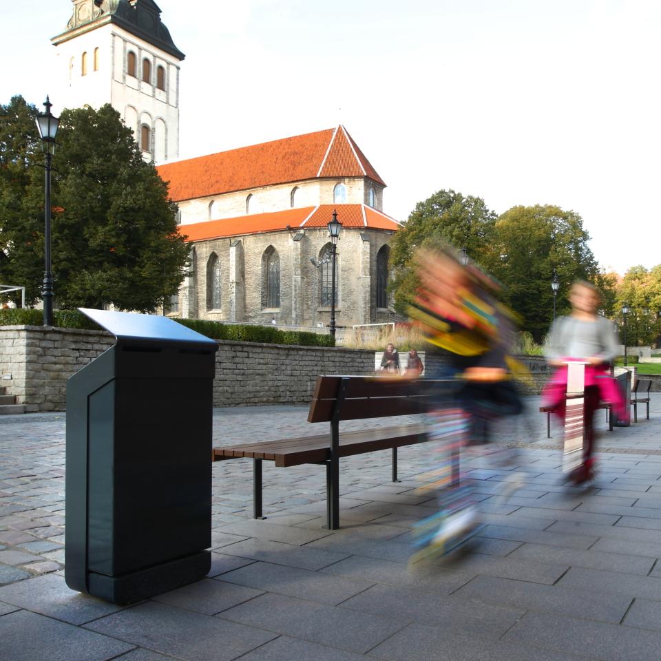 La fotografia mostra un cestino portarifiuti nove in una strada cittadina.