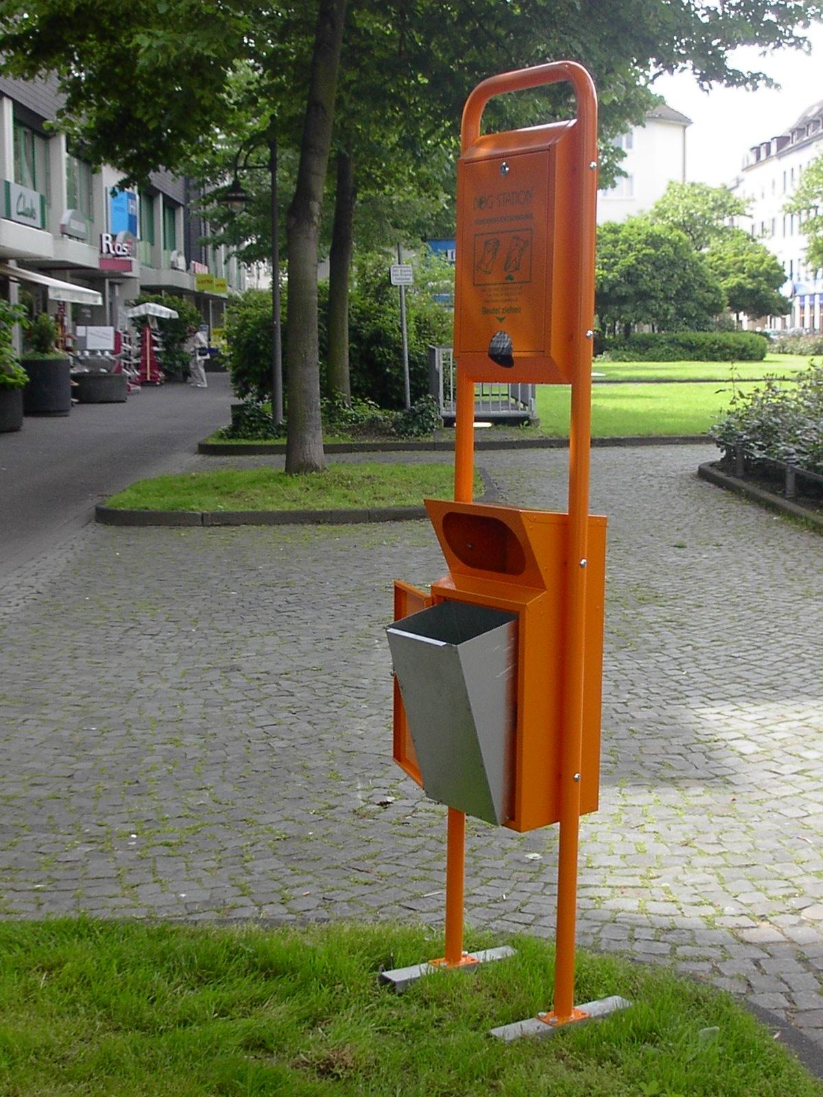 La fotografia mostra un contenitore per deiezioni canine M3, con dispenser sacchetti, in una strada cittadina.