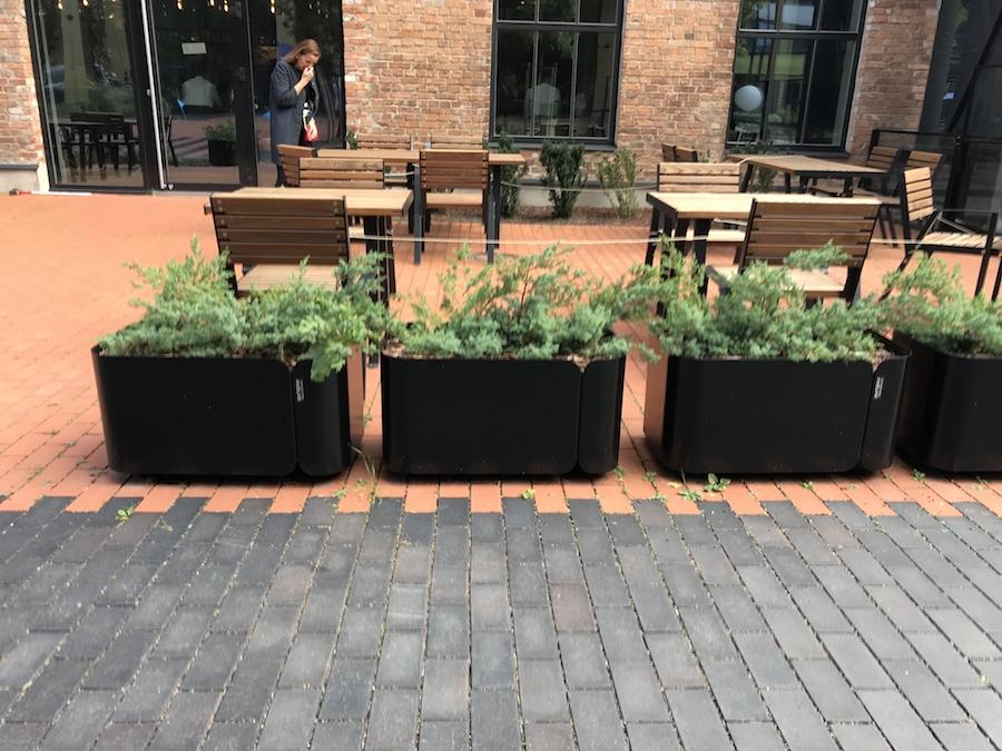 La fotografia mostra una fila di fioriere tiide, ai margini di un ristorante.
