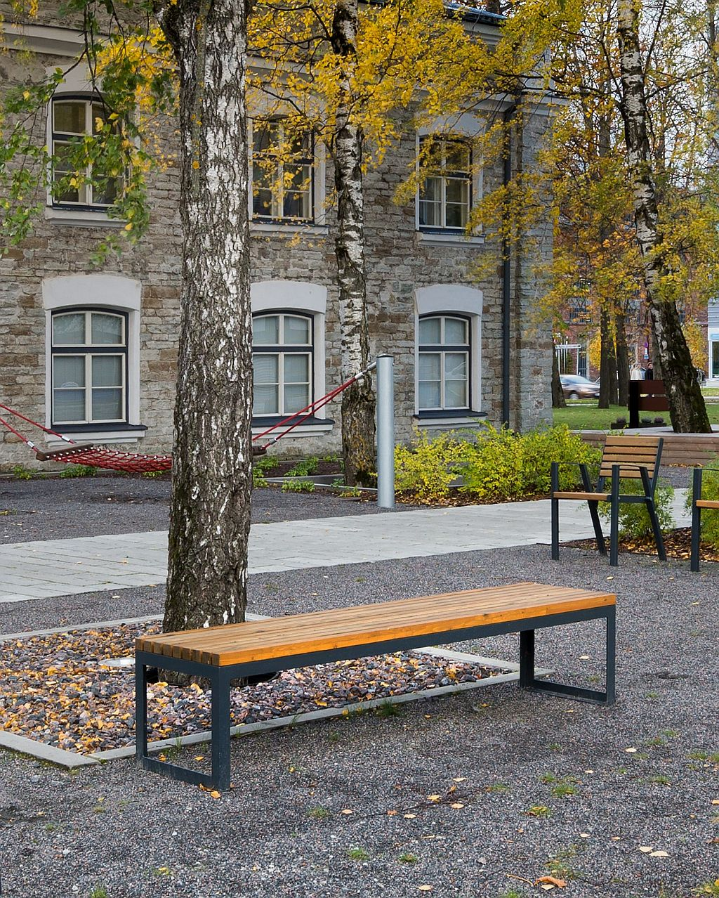 La fotografia mostra una panchina senza schienale club, all'esterno di un edificio storico.