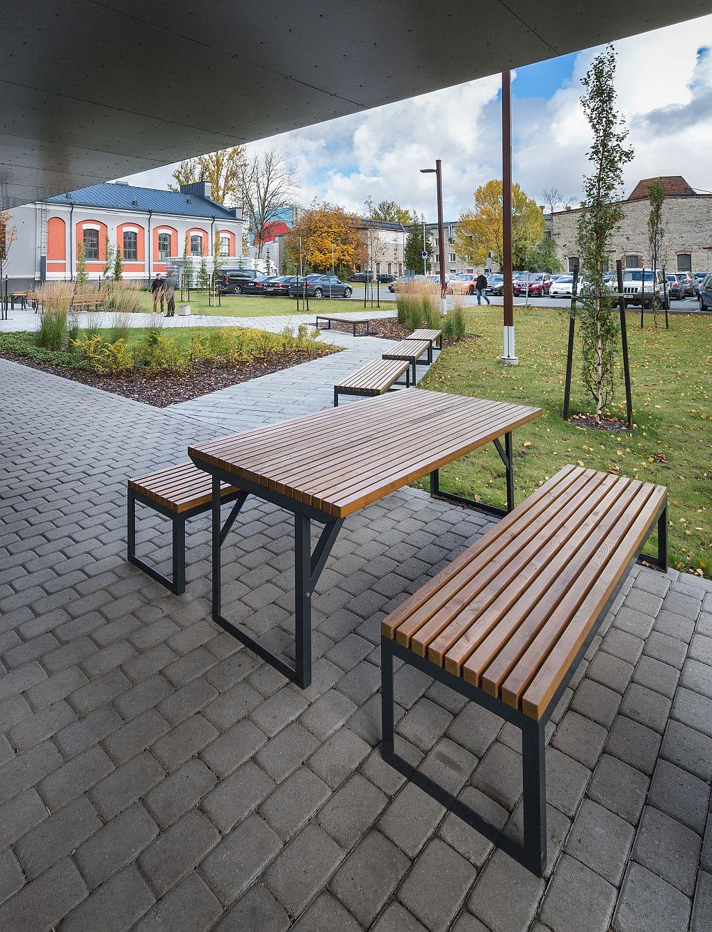 La fotografia mostra un set da picnic, con panchine e tavolo club, posto all'esterno di un esercizio di ristorazione.