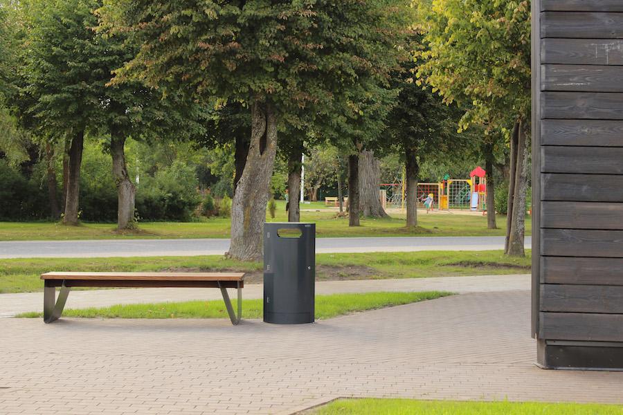 La fotografia mostra un cestino solo da 100 litri, accanto ad una panchina senza schienale tava, in un parco cittadino.