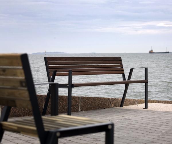 la fotografia mostra una panchina e una sedia della serie klaar in legno su una banchina.