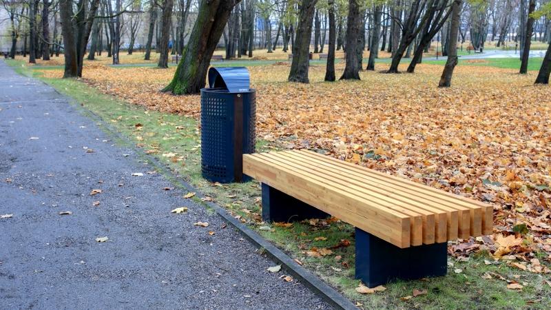 La fotografia mostra la panchina Nippon, con accanto il cestino portarifiuti Net, in un parco cittadino. Per dettagli sulla serie Extery Nippon, clicca sulla immagine.