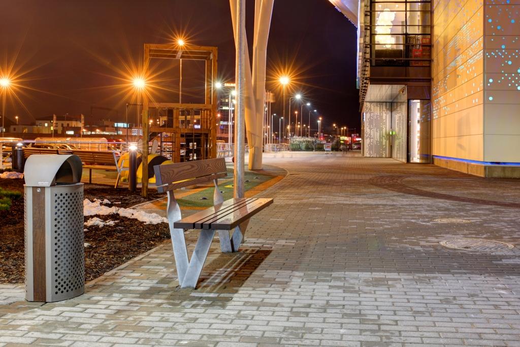 La fotografia mostra una panchina twist con accanto un cestino net, all'esterno di un centro commerciale.