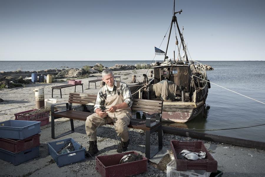 La fotografia mostra un pescatore intento a sistemare i suoi attrezzi, comodamente seduto su una panchina con schienale prima.