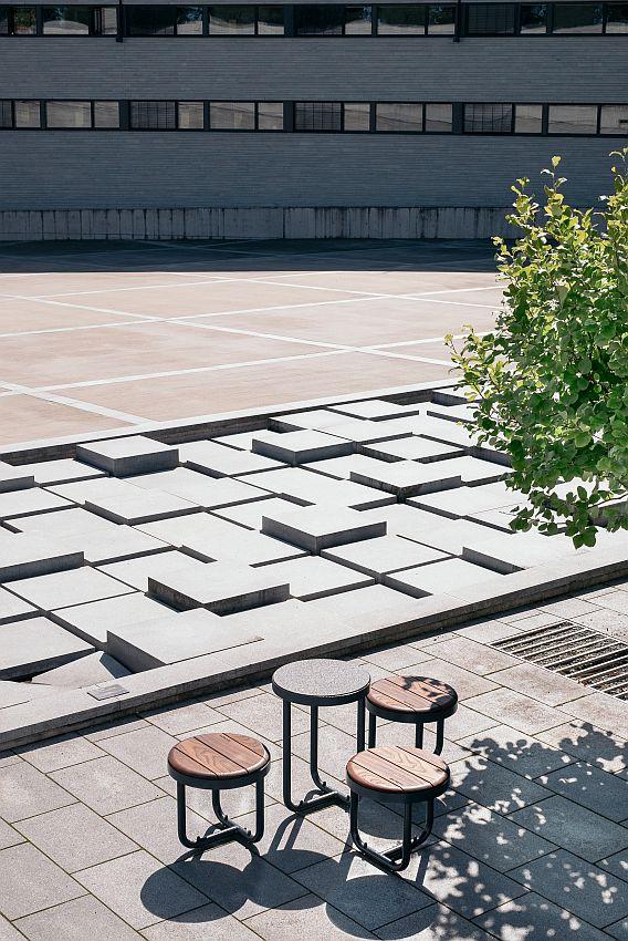 La fotografia mostra un set di sgabelli e tavolino della serie tiide, nel cortile di un edificio.