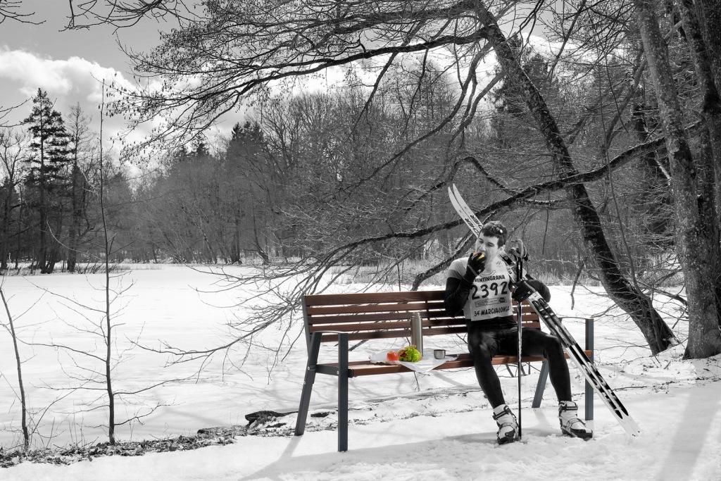 La fotografia mostra uno sciatore intento a consumare una merenda, comodamente seduto su una panchina klaar in legno e acciaio.