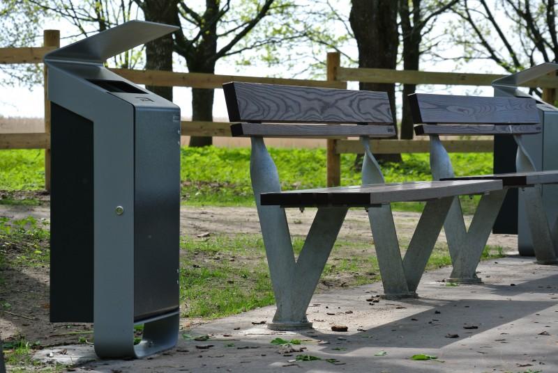 La fotografia mostra una panchina twist con accanto un cestino nove in una strada di periferia.