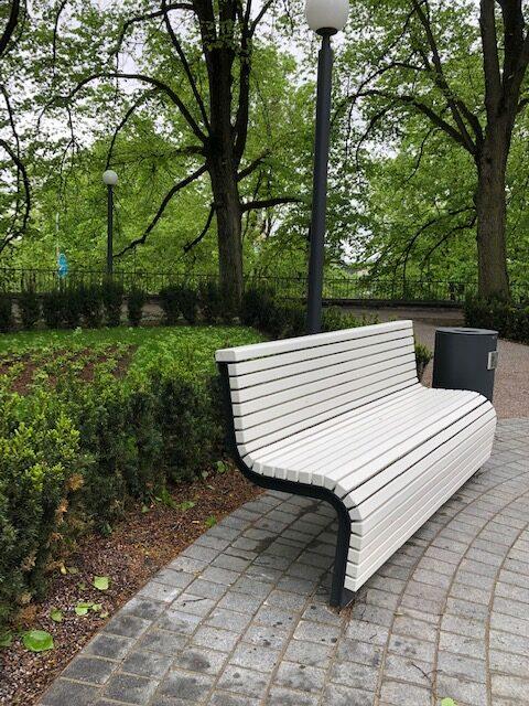 La fotografia mostra una panchina voog in un parco cittadino.