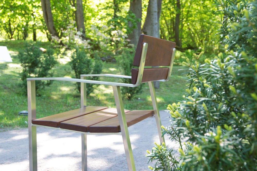 La fotografia mostra una sedia per esterni della serie linn in un parco.