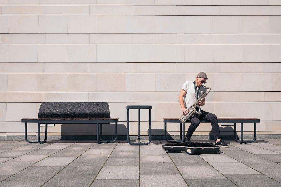 La fotografia mostra un set di panchine e tavolino della serie tiide all'esterno di un museo.